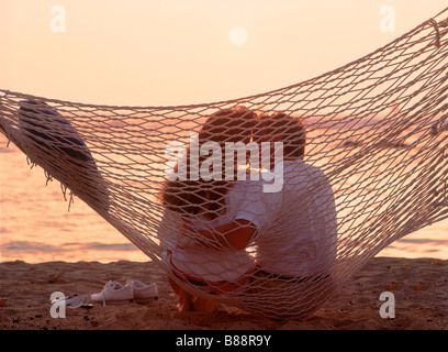 Couple sitting in beach hammock kissing at sunset - Stock Photo