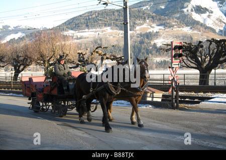 Austria EU January Austrian man driving a horse drawn sleigh alongside Zeller See lake - Stock Photo