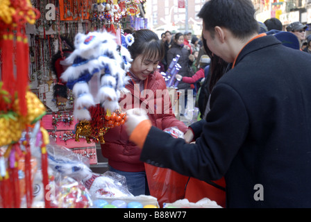 A merchant sells souvenirs in Chinatown during the annual Chinatown Lunar New Year Parade in New York - Stock Photo