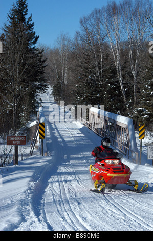 Snowmobile crossing a bridge in the Superior National Forest in winter. - Stock Photo