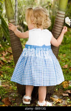 little girl standing next to palm tree - Stock Photo