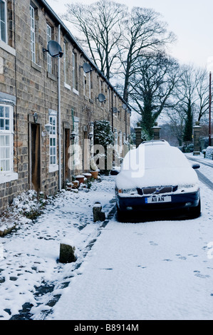 A car parked by its house on a snow covered street. - Stock Photo