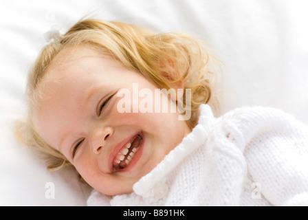 little girl lying on blanket laughing - Stock Photo
