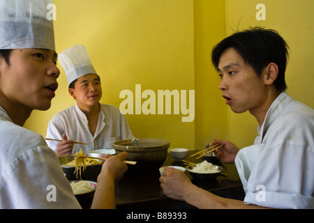 Chinese chefs have a rice and soup breakfeast in a Suzhou restaurant. - Stock Photo