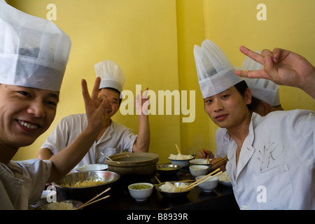 Chinese cooks pose and laugh at breakfast at their restaurant in Suzhou, China. - Stock Photo