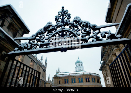 The gate leads to Sheldonian Theatre a Wren Building with Clarendon Building on the right in the snow - Stock Photo