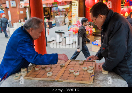 Two men playing a game of chinese checkers in Chinatown London UK - Stock Photo