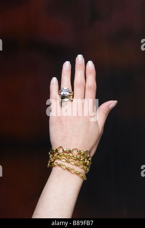 Woman wearing a big diamond ring and golden bracelets - Stock Photo