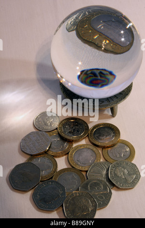 A photograph of a crystal ball magnifying part of a two pound coin  surrounded by other GBP coins in the background. - Stock Photo
