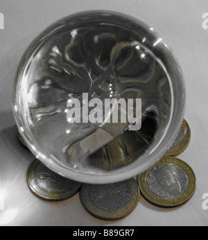 A photograph of a crystal ball magnifying part of a fifty pence piece, surrounded by two pound GBP coins in the - Stock Photo