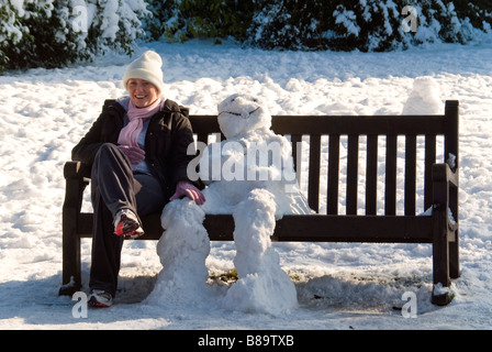 Humourous horizontal close up portrait of a traditional snowman and a young woman sitting on a park bench in the - Stock Photo