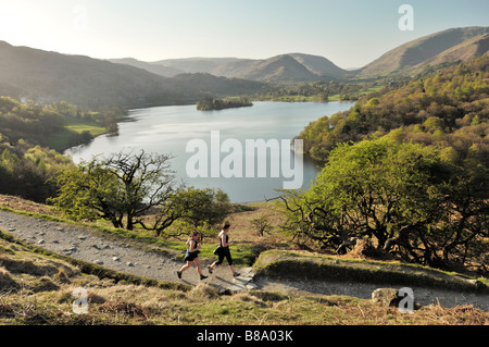 Joggers jogging running on Loughrigg Fell above Grasmere valley and lake in the Lake District National Park, Cumbria, - Stock Photo
