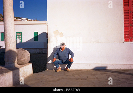 A fisherman on the Mediterranean island of Mykonos rests near port while waiting for his boat to arrive - Stock Photo
