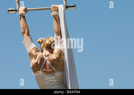 Female trapeze artist grips the bar - Stock Photo