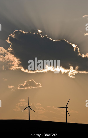 Two wind energy turbines stand silhouetted against the sky - Stock Photo