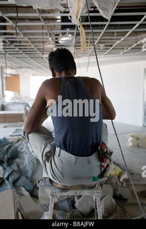 An electrician works on a construction site in Bangalore, India. - Stock Photo