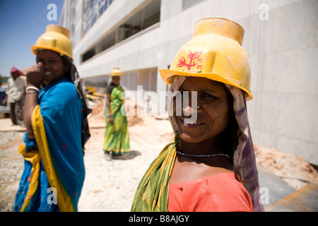 Women in yellow hard hats work on a construction site in Bangalore, India. - Stock Photo
