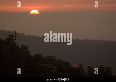 The sun sets over the valleys surrounding the north Indian town of Shimla. - Stock Photo