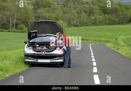 Woman alone with her broken down car on a country road - Stock Photo
