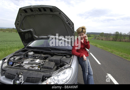 Car broken down with female driver alone phoning for help at the roadside - Stock Photo