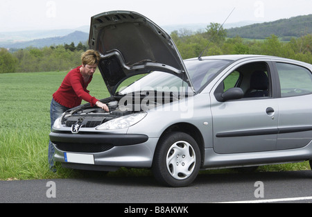 Broken down car on a country road - Stock Photo