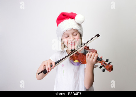 Girl - 6 years old  playing violin in Santa hat - Stock Photo