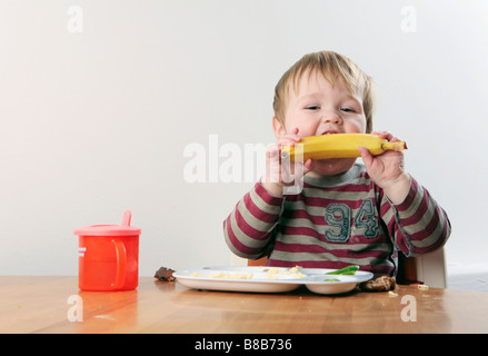 Baby boy eating at table (with signed model release - available for commercial use) - Stock Photo