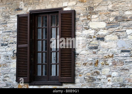Open window shutters over stone brick house wall in Upper Lefkara, South Cyprus - Stock Photo