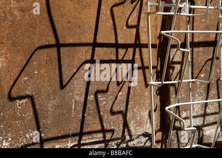 empty newspaper stand rack shadow on wall in sun - Stock Photo