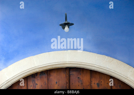Lamp over wooden  door  of old  house in Upper Lefkara, South Cyprus. - Stock Photo