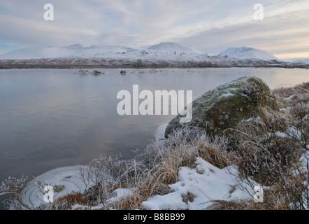 Looking across frozen Loch Ba to the snow covered Munro of Beinn a Chreachain Rannoch Moor Lochaber Scotland December