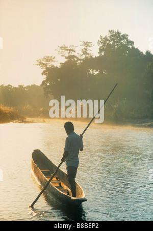 FV5216, Natural Moments Photography; Man dugout Boat, Chitwan National Park, Nepal - Stock Photo
