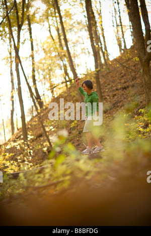 Woman balancing on fallen tree trunk in the woods - Stock Photo