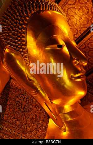 Face of reclining golden buddha statue in Wat Pho temple Phra Nakorn district in central Bangkok Thailand - Stock Photo