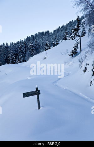 Wooden sign with snow covered path in the resort of Les Saises French Alpes