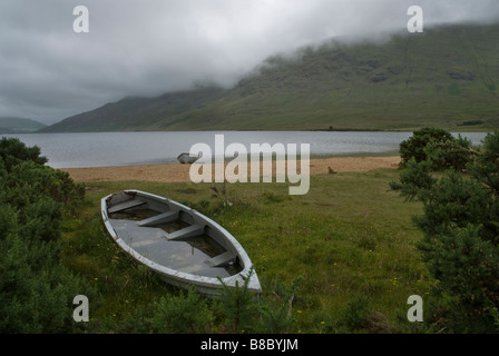 Waterlogged boat on the shore of Lough Nafooey, Ireland. - Stock Photo
