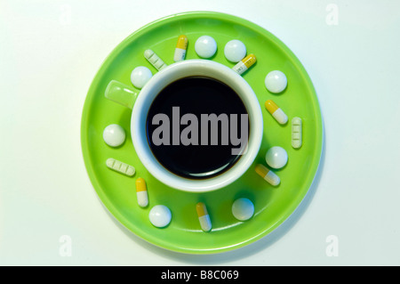 Doping at work. Coffee tablets and pills on a saucer next to a computer keyboard. - Stock Photo