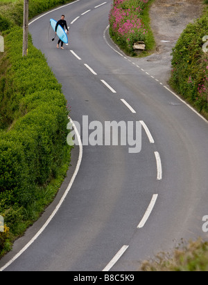 a lone surfer walks back from the beach along the Croyde coastal  road in Devon carrying his board - Stock Photo