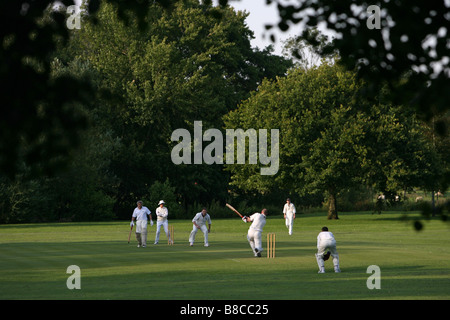 A Cricket Match being played in the English Countryside. - Stock Photo