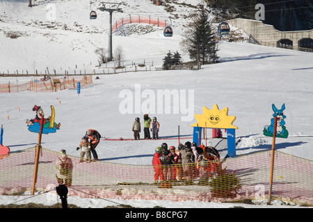 Rauris Austria EU January Group of young children having basic skiing lessons on the nursery slopes - Stock Photo