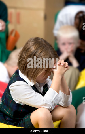 Elementary school girl with her head bowed in prayer. - Stock Photo