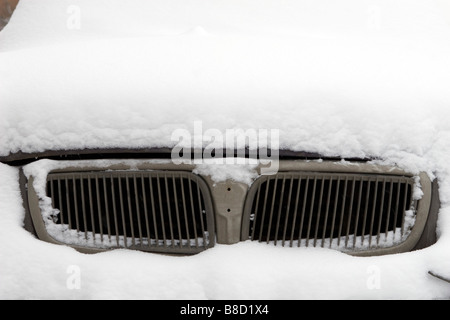 View of dirty chrome car air intake covered with snow. - Stock Photo