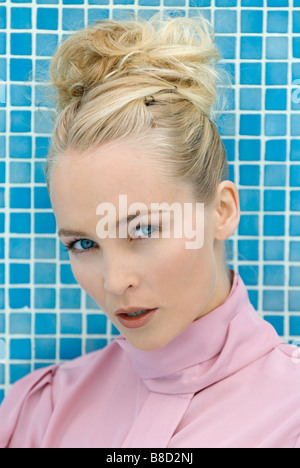 lose up of blue eyed blonde young woman in her twenties in front of blue tiles - Stock Photo