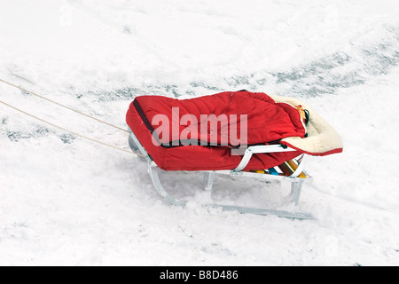 Sledge with red warm bag pulled by rope over snowy road. - Stock Photo