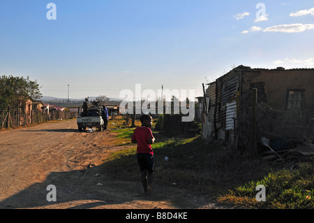 A young boy walks towards a 'bakkie' or pickup truck parked along a dirt road in a township area of Grahamstown, - Stock Photo