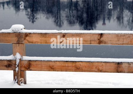 Wooden fence on not frozen winter river bank. - Stock Photo