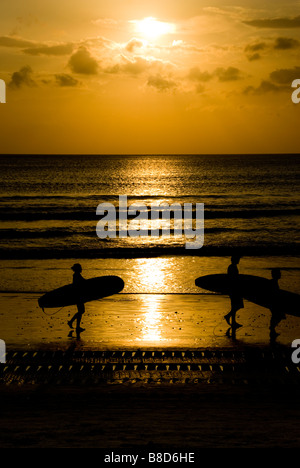 Surfers on Kuta Beach, Bali, at sunset - Stock Photo
