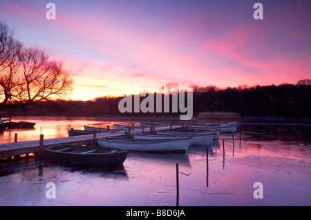 A winter sunrise over a frozen Ormesby Broad on the Norfolk & Suffolk Broads, UK - Stock Photo