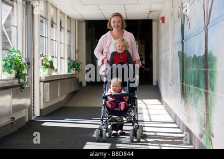 Mother with young boy and baby in stroller walk an elementary school hallway. - Stock Photo