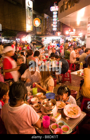 People eating at busy street corner restaurant - Thanon Yaowarat road in Chinatown central Bangkok Thailand - Stock Photo